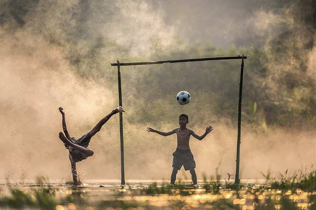 Asian children playing football in countryside