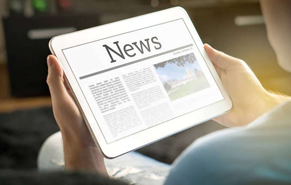 hands holding tablet with news page