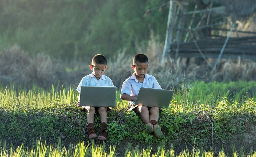 2 asian children with laptops in nature